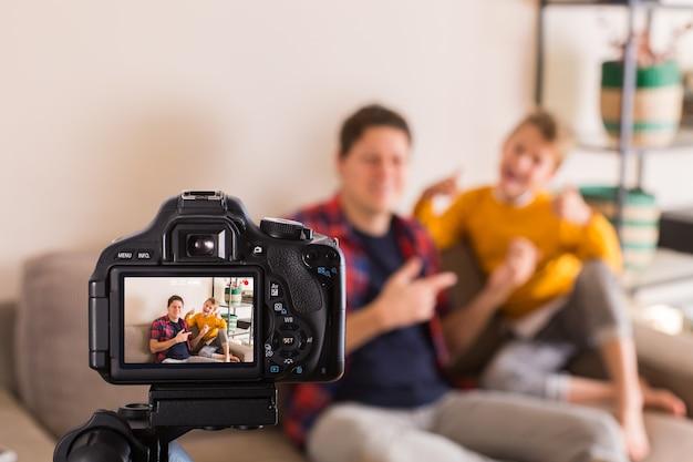 Família de vloggers gravando vídeo de mídia social enquanto está sentado no sofá