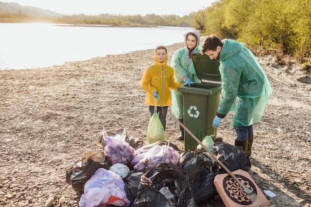 Família de voluntários com sacos de lixo, limpando o lixo ao ar livre. conceito de ecologia. praia limpa juntos.