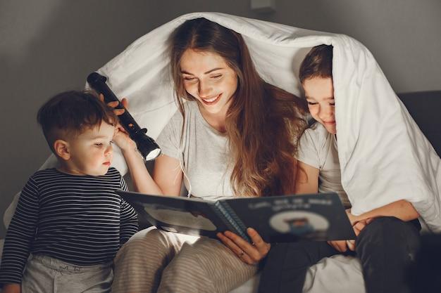 Família debaixo do cobertor na cama lendo um livro.