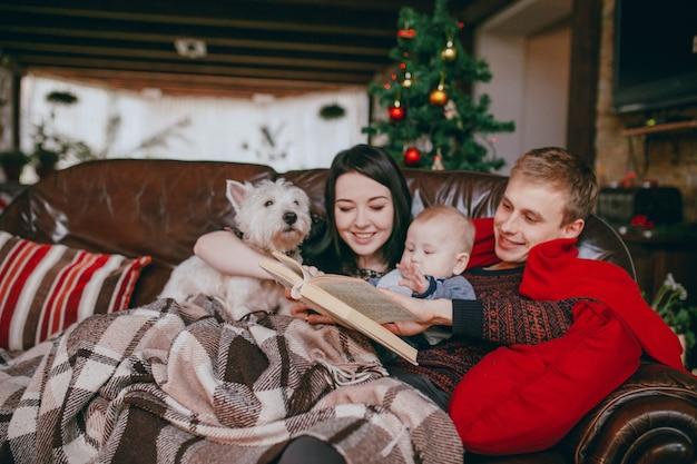 Família deitada em um sofá com um cobertor enquanto lêem um livro