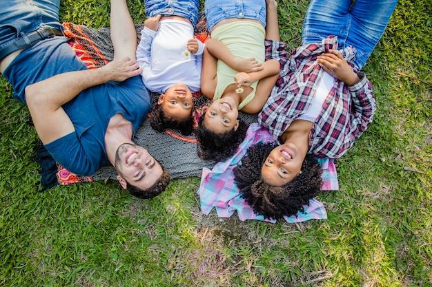 Família deitada na grama olhando para o céu
