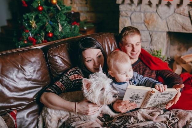 Família deitado no sofá coberto com um cobertor, enquanto eles olham para um livro