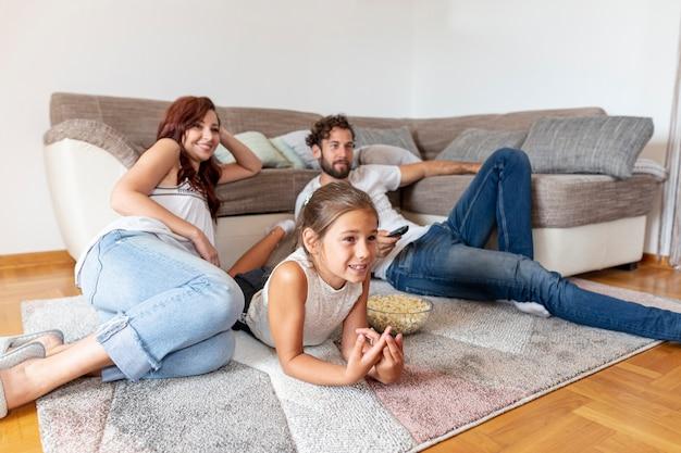 Família, deitando, chão, enquanto, olhando tv