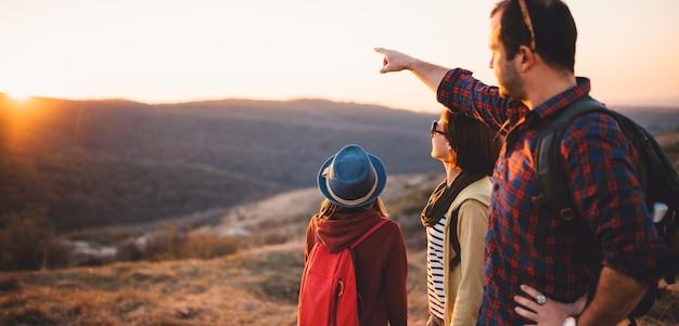 Família descansando na montanha depois de caminhadas durante o pôr do sol