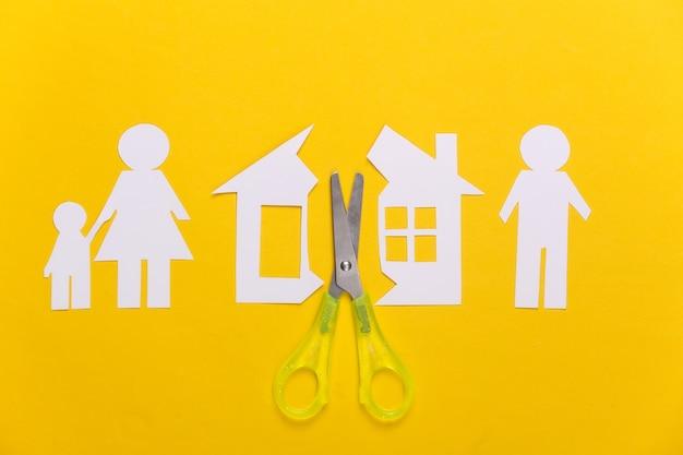 Família desfeita, divórcio. conceito de divisão de propriedade. casa de papel com corte em tesoura, família em amarelo