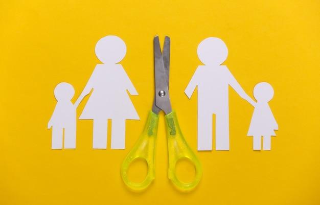 Família desfeita, divórcio. família de papel cortado em tesoura em amarelo