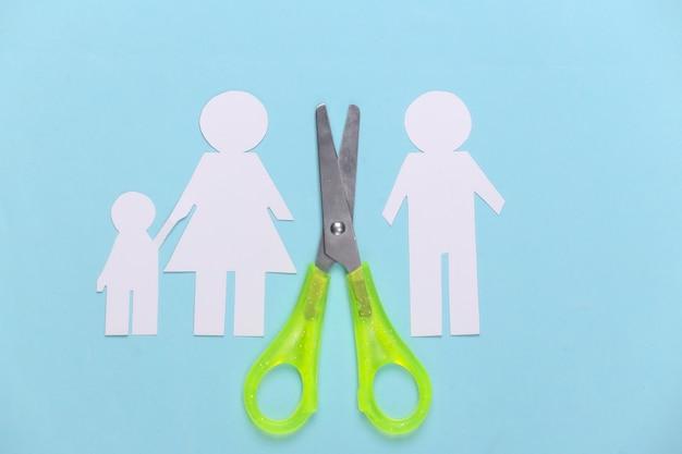 Família desfeita, divórcio. família de papel cortado em tesoura em azul pastel
