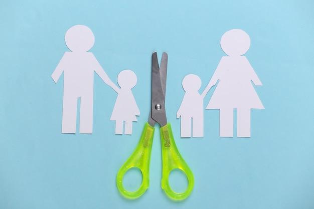 Família desfeita, divórcio. família de papel cortado em tesoura em azul