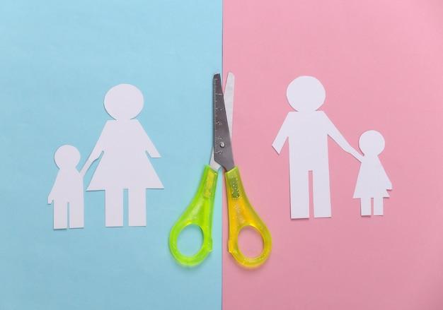 Família desfeita, divórcio. família de papel cortado em tesoura em pastel rosa azul
