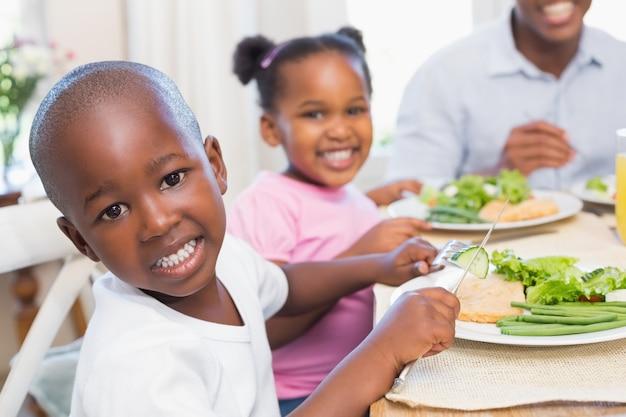 Família, desfrutando, saudável, refeição, junto, filho, sorrindo, câmera