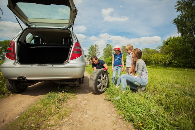 Família divertida está em um piquenique. uma avaria no carro.