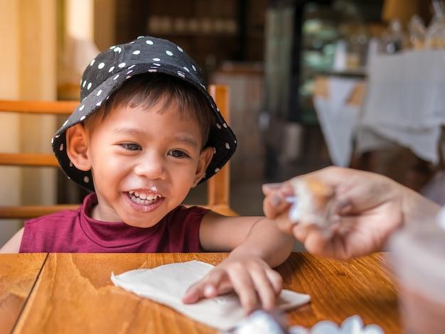 Família do bebê muito do divertimento da mãe asiática que alimenta a padaria a sua filha bonito.