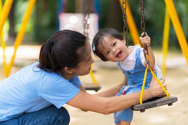 Família do estilo de vida, mamã feliz e filha que apreciam o tempo no campo de jogos no parque