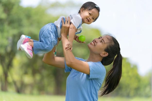 Família do estilo de vida, mamã feliz e filha que apreciam o tempo no parque