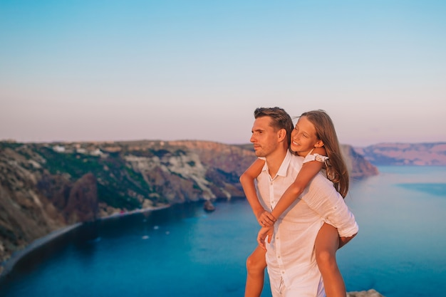 Família do pai e da filha à beira de um penhasco ao pôr do sol