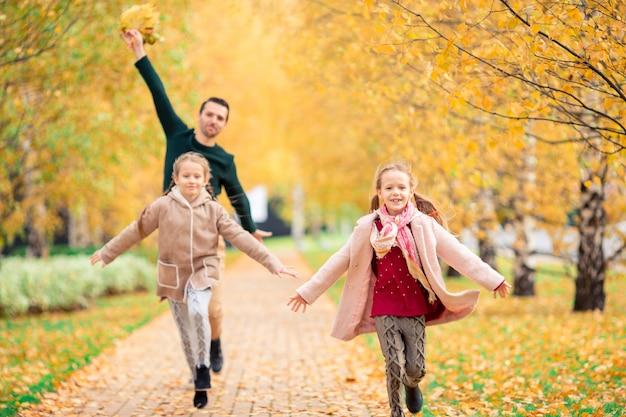 Família do pai e filhos no lindo dia de outono no parque