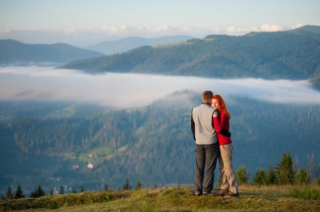 Família do turista - homem e mulher que abraçam e que apreciam a paisagem bonita da montanha com névoa da manhã sobre as montanhas e as florestas. garota ruiva, olhando para a câmera