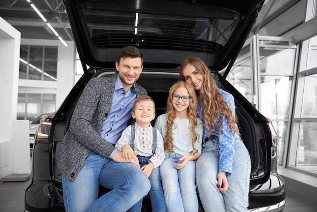 Família doce sentados juntos no porta-malas no carro e posando