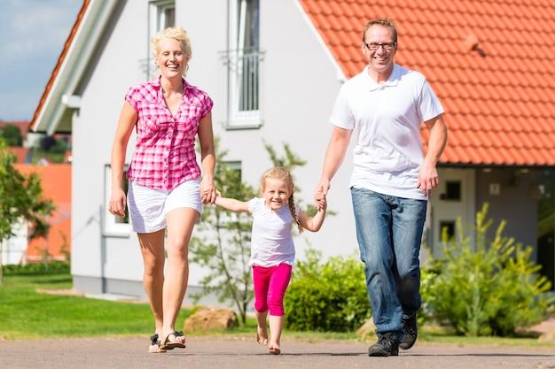 Família dos pais e criança andando em frente de casa em uma vila ou subúrbio