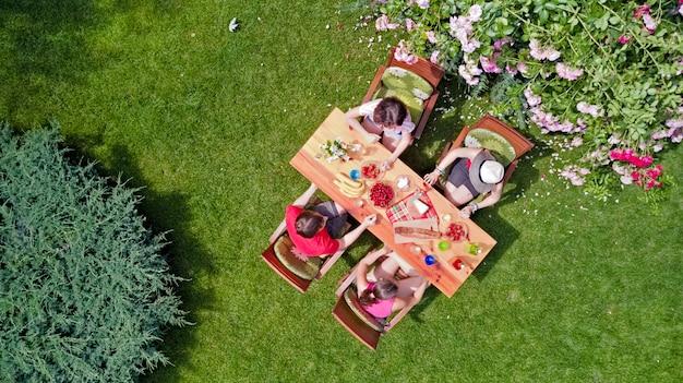 Família e amigos comendo juntos ao ar livre na festa de verão. vista aérea da mesa com alimentos e bebidas de cima. conceito de lazer, férias e piquenique