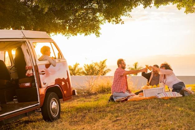 Família e amigos reunidos em um piquenique de atividades de lazer em um prado com uma velha van vintage vermelha estacionada e filhos filhos dentro dele, olhando-os tilintando algumas cervejas durante um pôr do sol dourado colorido