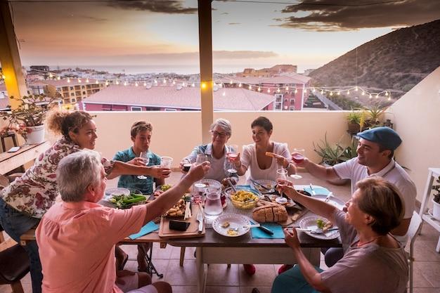 Família e amigos se divertem juntos, brindando e brindando com taças de vinho