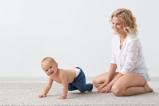 Família e conceito de parentalidade bebê fofo brincando com a mãe no tapete bege