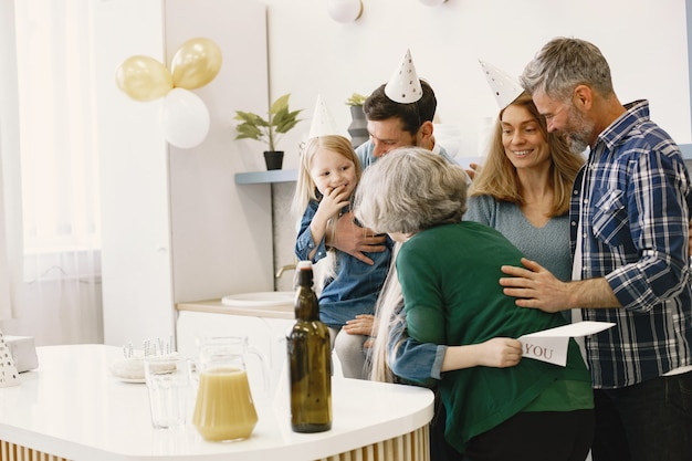 Família e duas filhas comemoram aniversário da avó menina abraçando a avó