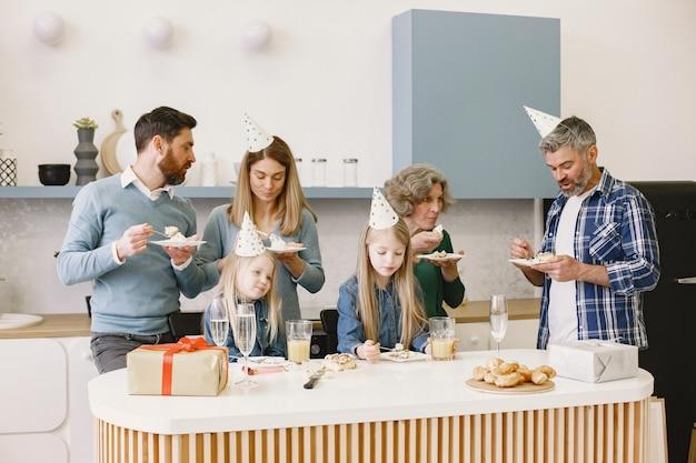 Família e duas filhas comemoram aniversário da avó. pessoas estão comendo bolo