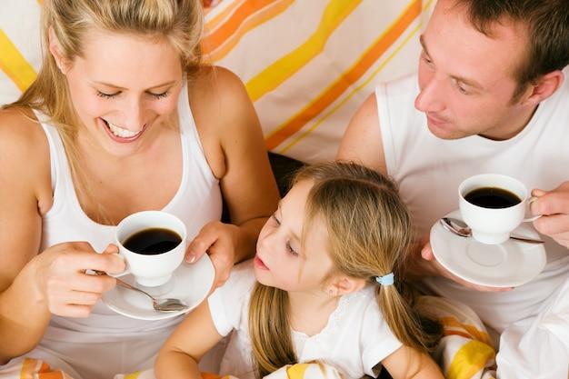Família e gato tomando café da manhã na cama