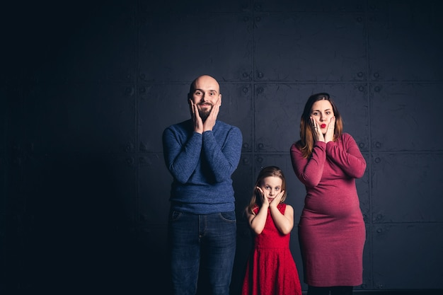 Família elegante segurando seus rostos