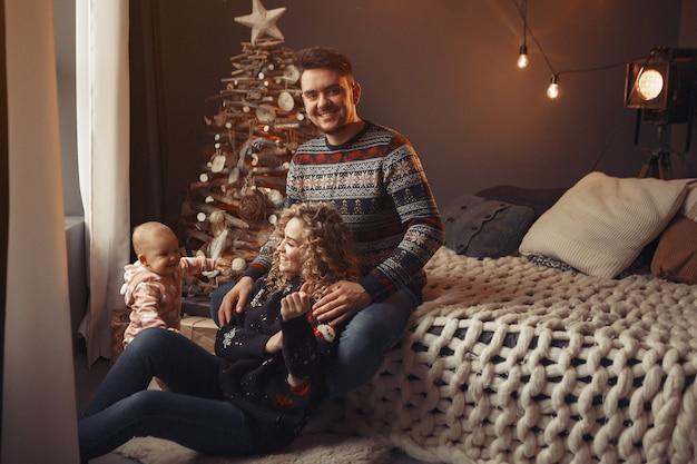 Família elegante sentada em casa perto da árvore de natal