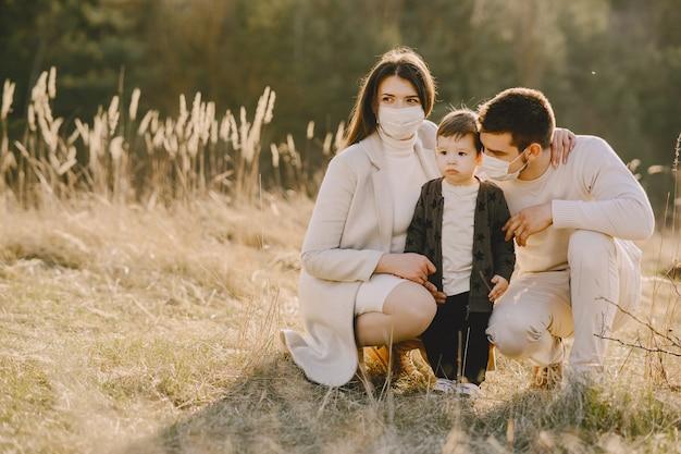 Família elegante vestindo máscaras andando em um campo de primavera