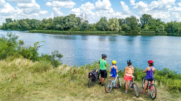 Família em bicicletas andando de bicicleta ao ar livre pais ativos e filhos em bicicletas vista aérea de família feliz