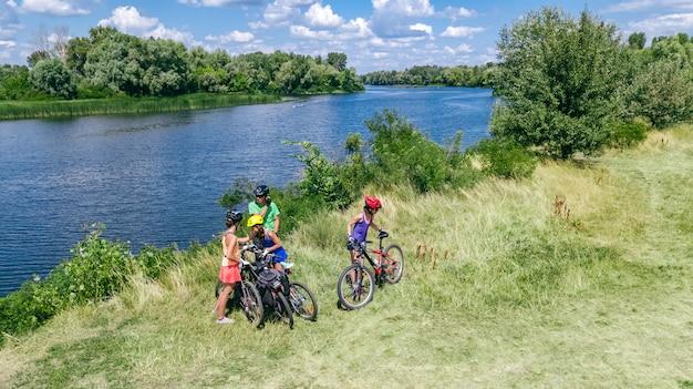 Família em bicicletas, andar de bicicleta ao ar livre, pais ativos e crianças em bicicletas, vista superior aérea da família feliz com crianças relaxantes perto do rio bonito de cima, conceito de esporte e fitness