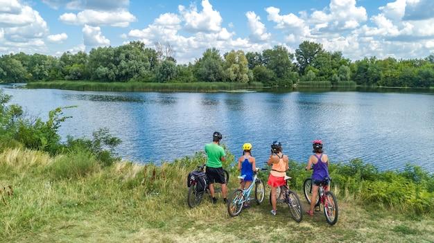 Família em bicicletas, andar de bicicleta ao ar livre, pais e filhos em bicicletas, vista superior aérea da família feliz