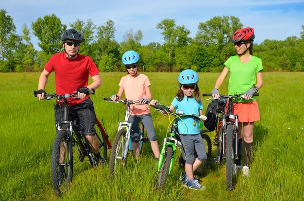 Família em bicicletas ao ar livre, felizes pais ativos e dois filhos, andar de bicicleta no prado primavera, esporte, fitness e conceito de estilo de vida saudável