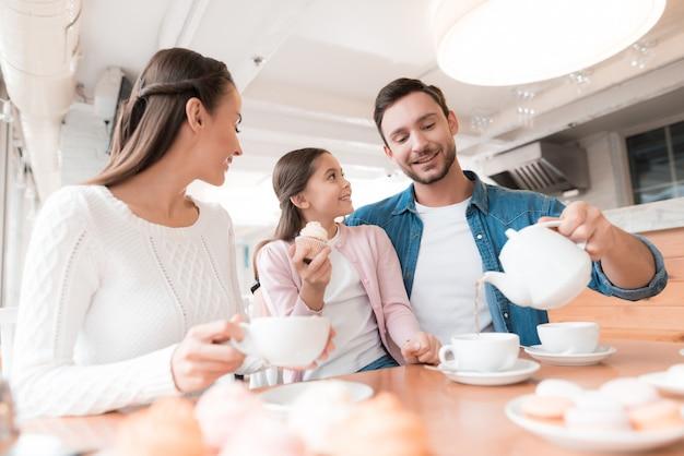 Família em cafe dad pours tea kid tem cupcake.