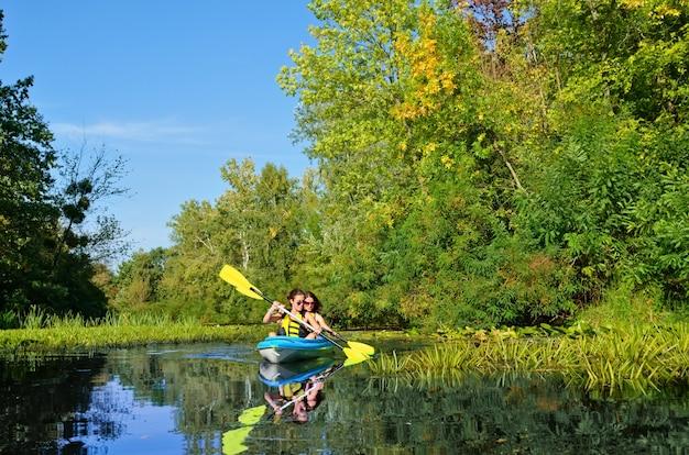 Família em caiaque, mãe e filha remando em caiaque em passeio de canoa no rio se divertindo, fim de semana ativo e férias com crianças, conceito de fitness