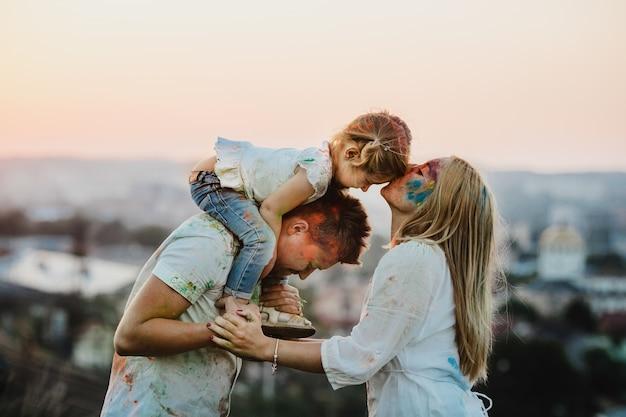 Família, em, camisas brancas, coberto, com, diferente, tintas, plataformas, exterior, à noite