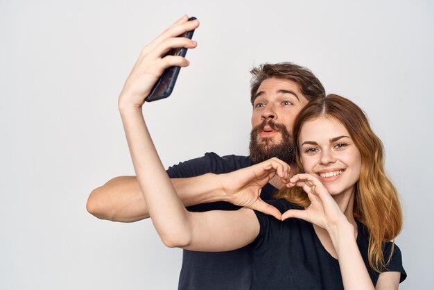 Família em camiseta preta telefone diversão juntos amizade fundo isolado