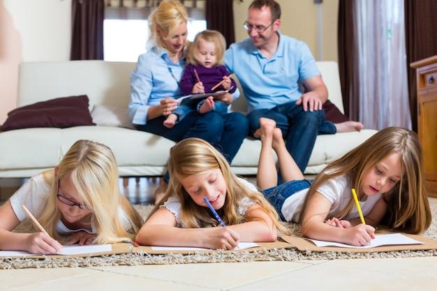 Família em casa, as crianças colorindo no chão
