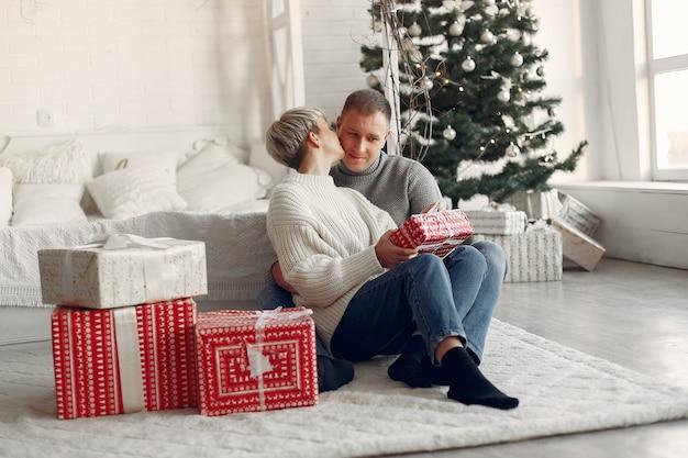 Família em casa. casal perto de decorações de natal. mulher com um suéter cinza.