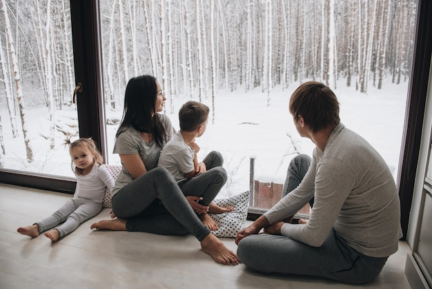 Família em casa de pijama. filha e filho. acorde de manhã. abraçando e beijando, olhando pela janela. lindo inverno fora da janela. grandes janelas para o chão. bela vista da janela.