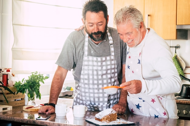 Família em casa no trabalho na cozinha com pai maduro sênior e filho adulto preparando um bolo juntos como amigos - diversidade e gerações mistas na casa