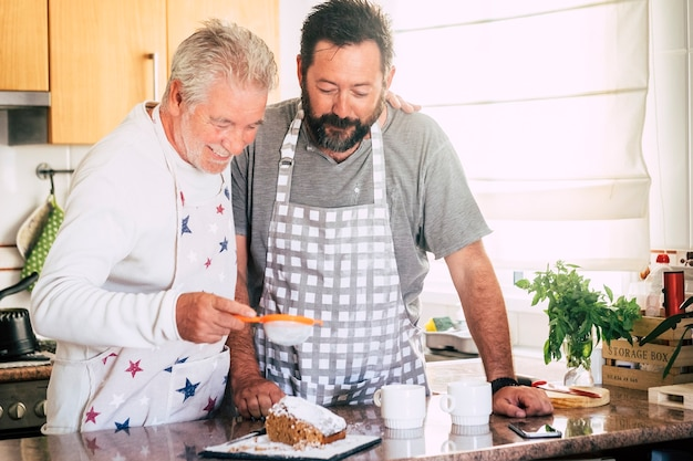 Família em casa no trabalho na cozinha com pai maduro sênior e filho adulto preparando um bolo juntos como amigos