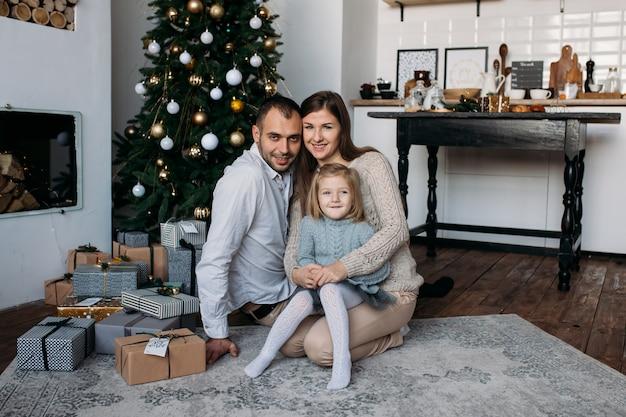 Família em casa perto de árvore de natal e presentes de natal