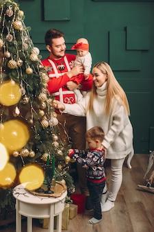 Família em casa perto de árvore de natal