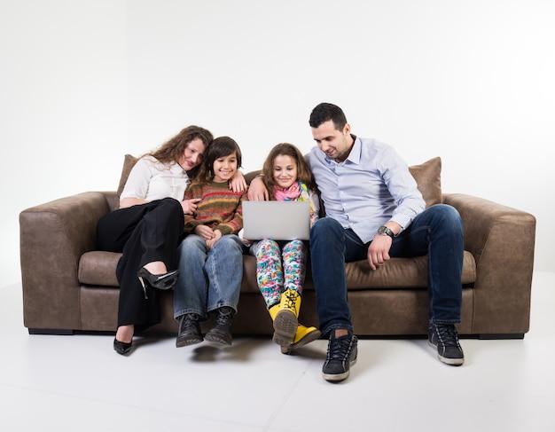Família em casa sentado no sofá