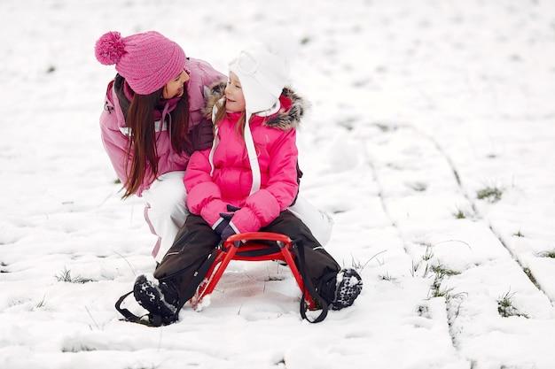 Família em chapéus de malha de inverno nas férias de natal em família. mulher e menina em um parque. pessoas brincando com trenó.